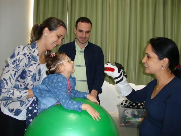 Imagem da terapeuta ocupacional posicionando uma criança com baixa visão sobre uma bola suiça e a sua frente a mãe apresentando fantoche e ao fundo o pai observando.