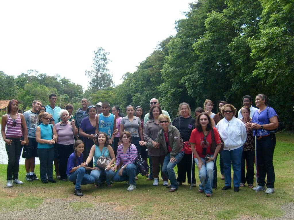 Imagem de 29 pessoas, entre participantes e colaboradores da PARA-D.V.,  num gramado com árvores ao fundo durante um passeio na cidade de Socorro.